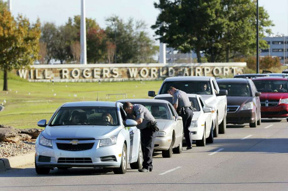Oklahoma City police officers gather information from vehicles leaving Will Rogers World Airport, Tuesday, Nov. 15 2016, in Oklahoma City. The airport was put on lockdown after a shooting at the main terminal. Photo: Steve Gooch — The Oklahoman Via AP / The Oklahoman