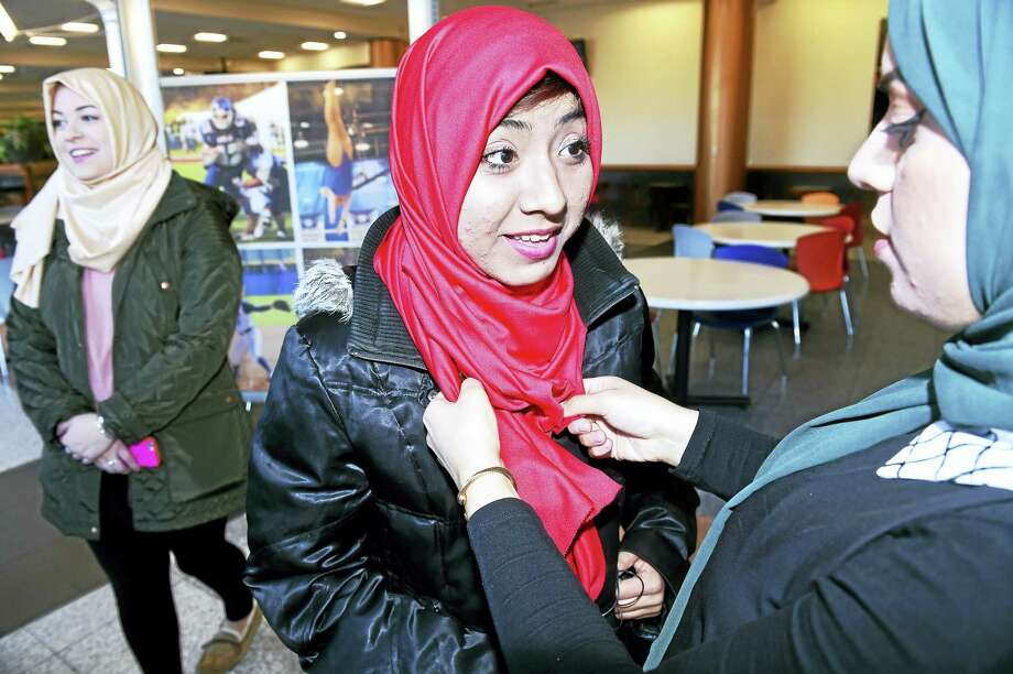 Junior Bahar Musa, right, of the Muslim Student Association adjusts a hijab on Bethzua Garcia, center, of Bridgeport during a Hijab Day event at the Adanti Student Center at Southern Connecticut State University in New Haven Monday. Garcia is an incoming freshman. At left is senior Molly Murphy. Photo: Arnold Gold — New Haven Register