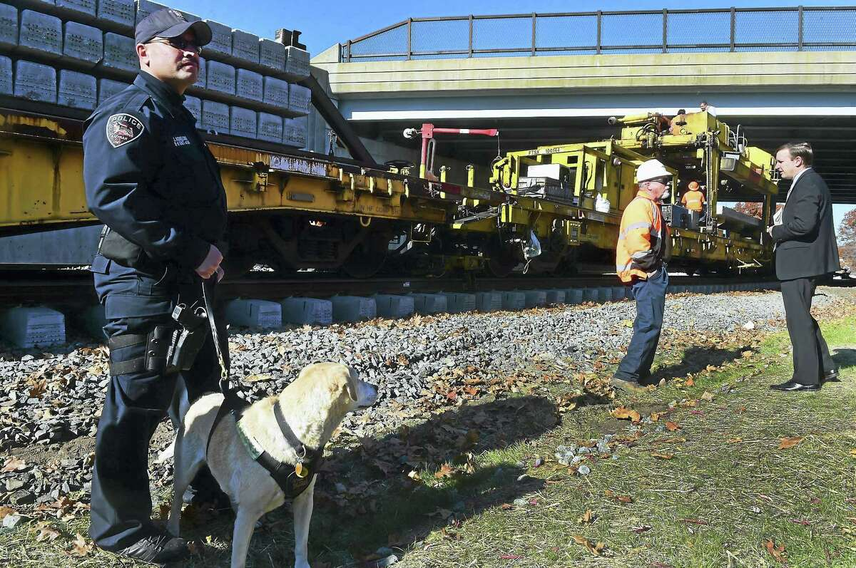 U.S. Sen. Chris Murphy, right, talks with an Amtrak supervisor under the protective eye of Amtrak Police Officer Joseph E. Agnellino and his canine partner Roxy Monday morning as Murphy visits the Hartford Rail Line in Wallingford.