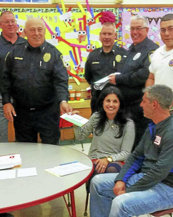 From left, Seymour schools Director of Security Richard Kearns, Police Chief Michael Metzler, Deputy Police Chief Paul Satkowski, Community Police Officer John Harkins and Officer Jonathan Martin; and seated, parents Jennifer and Yugo Ferreira. Photo: JEAN FALBO SOSNOVICH — NEW HAVEN REGISTER