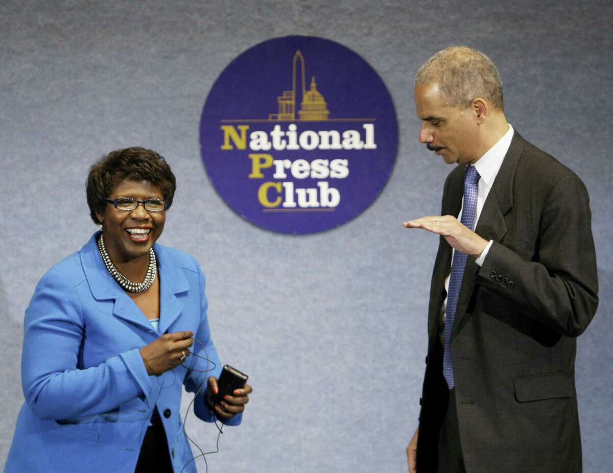 In this file photo, then-Attorney General Eric Holder talks with Gwen Ifill during a NAACP Legal Defense and Educational Fund luncheon at the National Press Club in Washington. Ifill died on Monday of cancer, PBS said. She was 61.