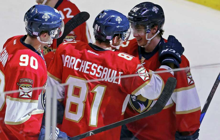 Florida Panthers center Jonathan Marchessault (81) celebrates with teammate Denis Malgin (62) who scored the winning goal in overtime to defeat the New York Islanders in an NHL hockey game, Saturday, Nov. 12, 2016, in Sunrise, Fla. Panthers center Jared McCann (90) looks on. (AP Photo/Joe Skipper) Photo: AP / FR171174 AP