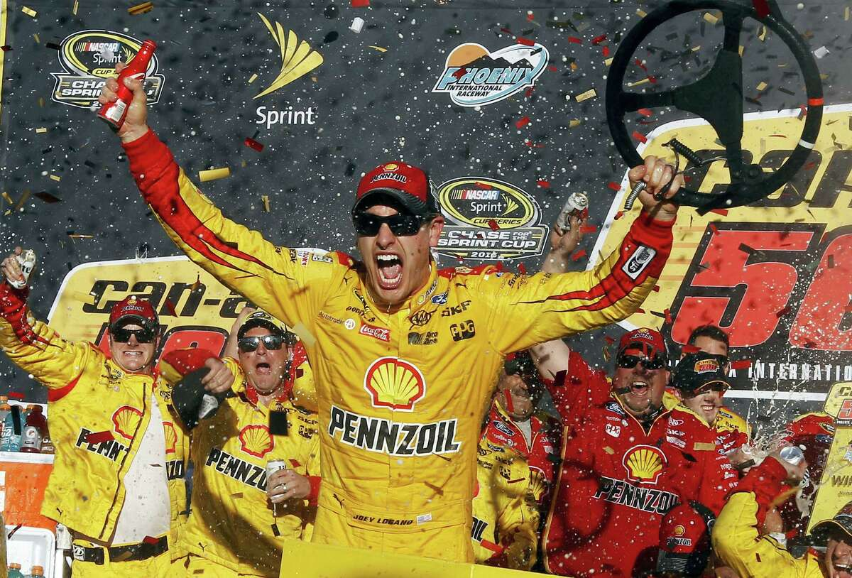 Joey Logano celebrates in the victory lane after winning the NASCAR Sprint Cup Series race at Phoenix International Raceway Sunday in Avondale, Ariz.