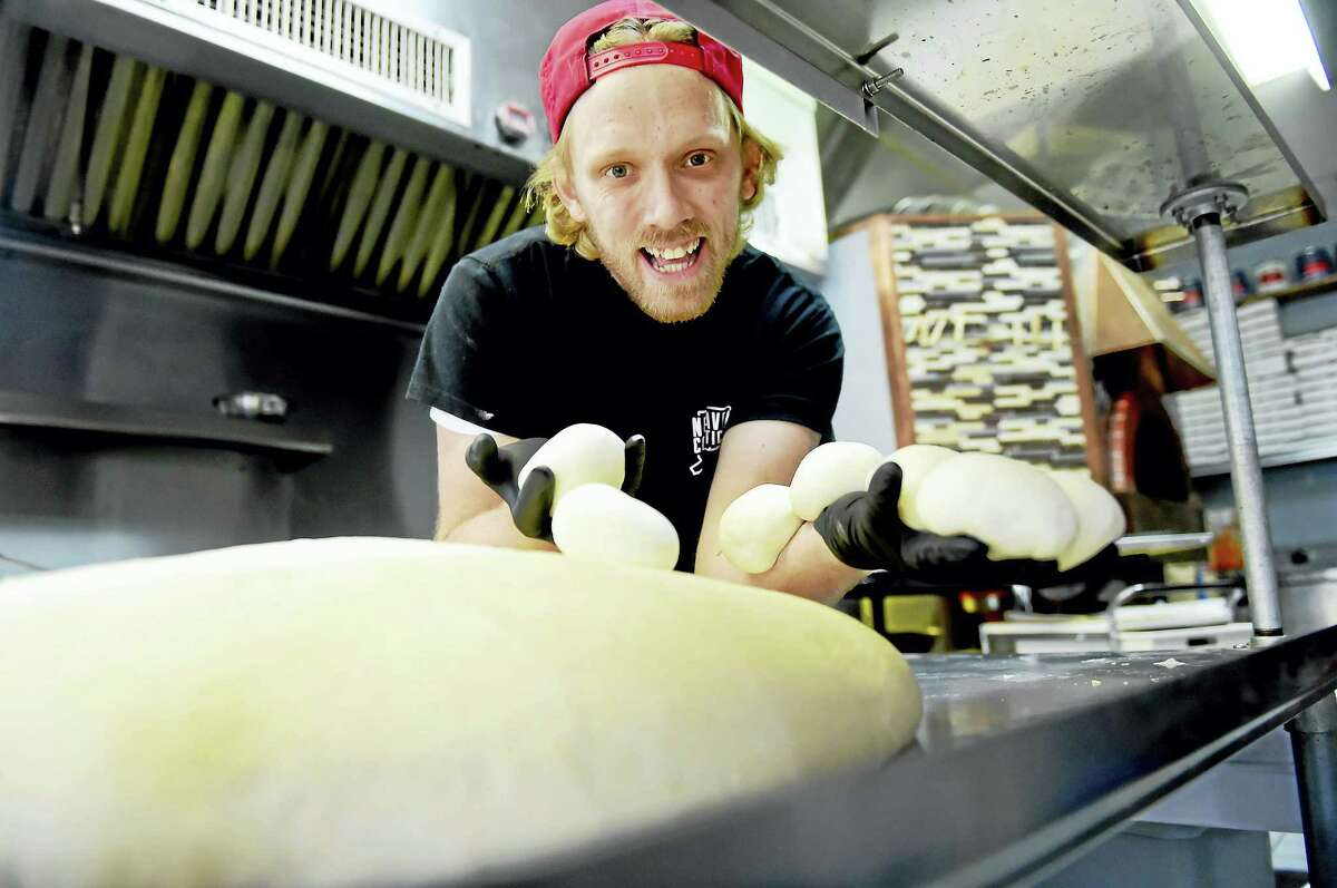 Andrew Holmes, part owner of One 6 Three The Pizza Joint with pizza dough at his restaurant on Foster Street in New Haven .