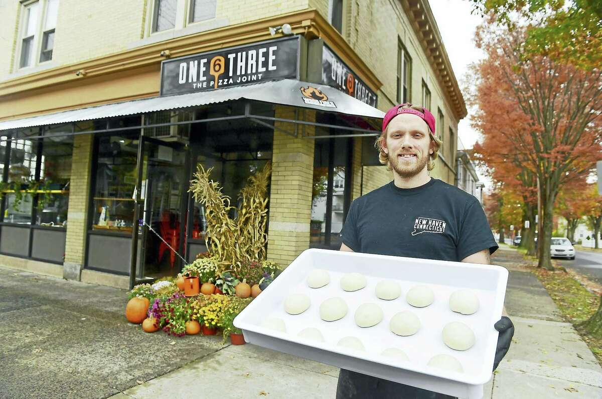 Andrew Holmes, part owner of One New6 Three The Pizza Joint with pizza dough at his restaurant on Foster Street in New Haven.