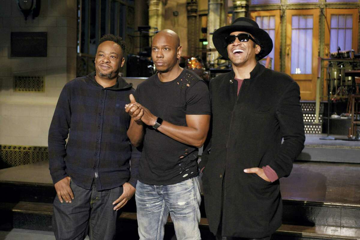 """In this Nov. 10, 2016 photo released by NBC, Jarobi White and Q-Tip of musical guest A Tribe Called Quest pose with host Dave Chappelle, center, on the television show, """"Saturday Night Live,"""" in New York. """"Saturday Night Live"""" called on host Chappelle's wit for a thoughtful coda to a divisive presidential campaign. Chappelle offered an African-American take on President-elect, Donald Trump's victory over Hillary Clinton, saying he hadn't seen white people so mad since the O.J. Simpson verdict."""