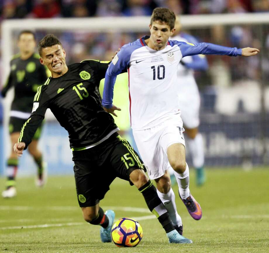 Mexico's Hector Moreno, left, and United States' Christian Pulisic chase a loose ball during the first half of a World Cup qualifying soccer match Friday in Columbus, Ohio. Photo: Jay LaPrete — The Associated Press   / FR52593 AP