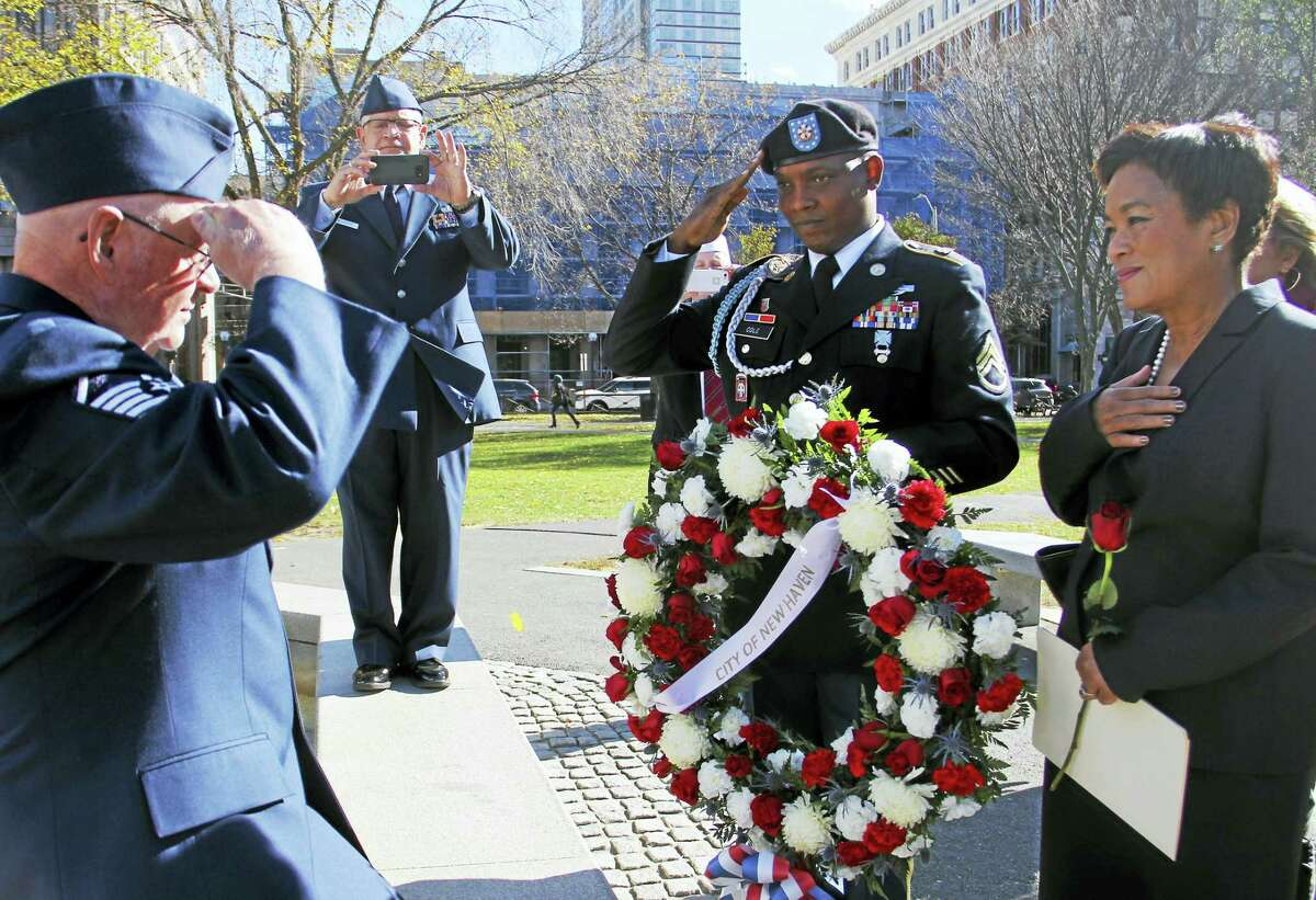 New Haven police officer and Connecticut Army National Guard Staff Sgt. Dennis Cole salutes a fellow veteran while standing next to Mayor Toni Harp during a laying of wreaths commemorating Veterans Day on the Green. Cole also serves as Harp's security officer.