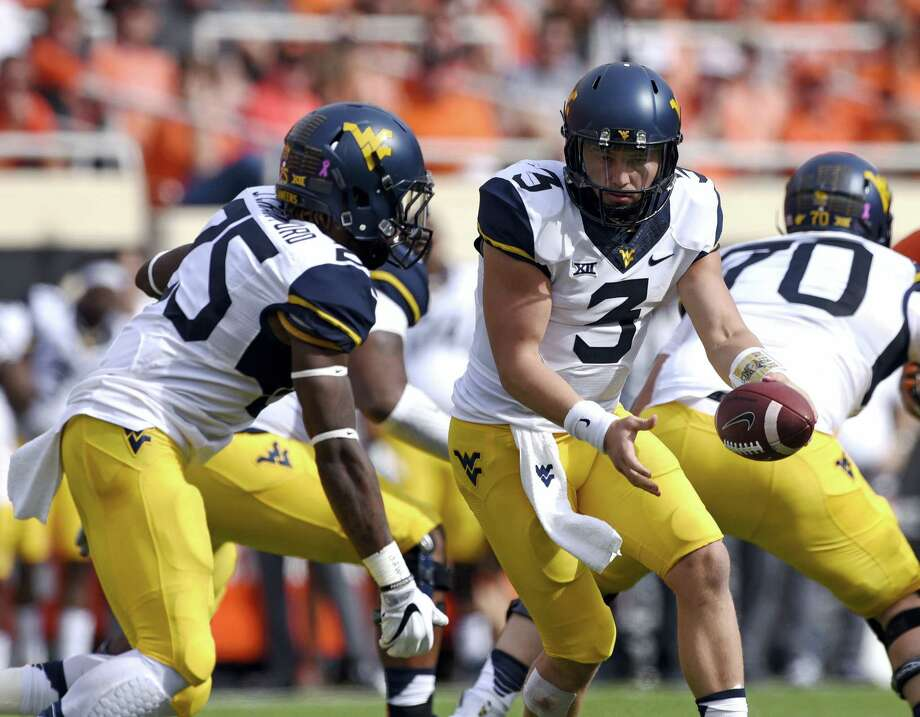 In this Oct. 29, 2016 photo, West Virginia quarterback Skyler Howard (3) hands off to running back Justin Crawford during the team's NCAA college football game against Oklahoma State in Stillwater, Okla. West Virginia travels to play Texas this week. Photo: AP Photo/Brody Schmidt, File   / FR79308 AP