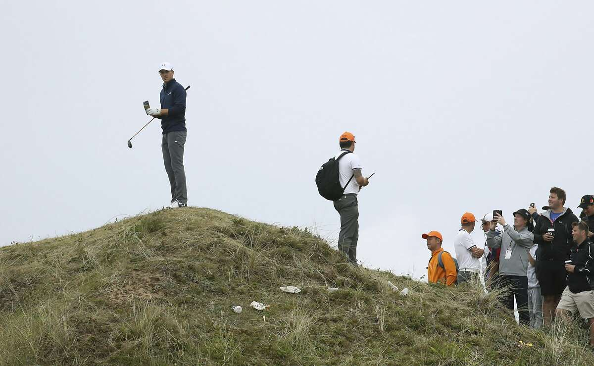 Jordan Spieth of the United States, left, stands on a mound to look at his ball on the 13th hole during the final round of the British Open Golf Championship, at Royal Birkdale, Southport, England, Sunday July 23, 2017. (AP Photo/Peter Morrison)