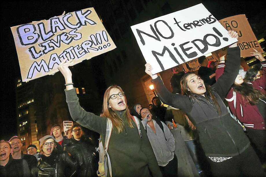 New York City resident Christina Martin, left, a student at Yale School of Nursing, was among hundreds of people protesting the victory of President-elect Donald Trump Thursday in front of the U.S. District Courthouse at 141 Church St. in New Haven. Photo: Catherine Avalone — New Haven Register   / New Haven RegisterThe Middletown Press