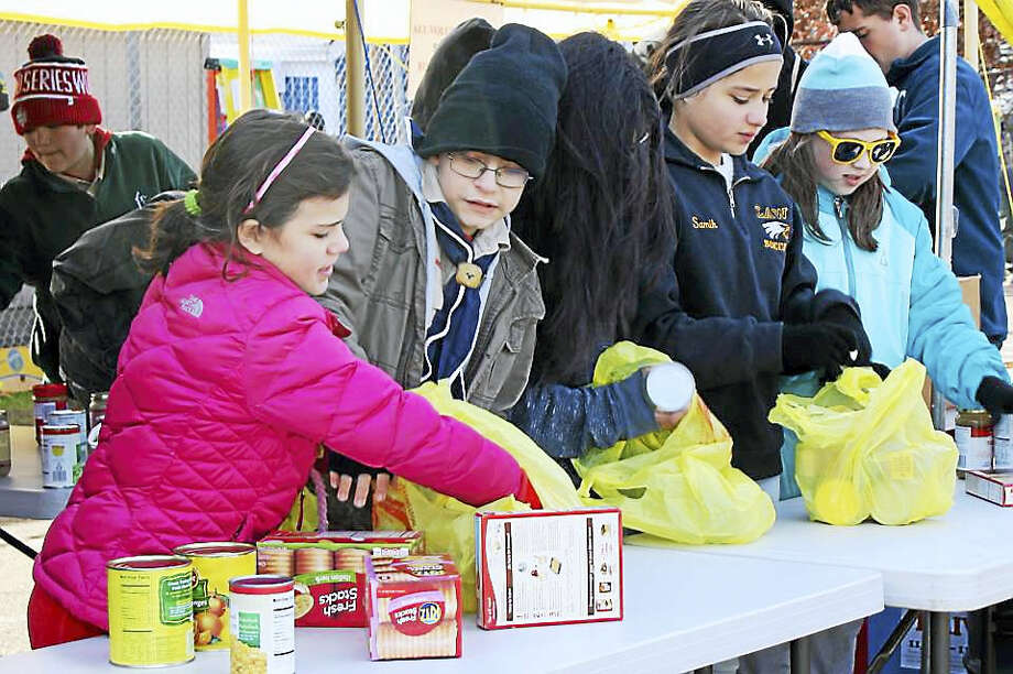 Volunteers sort food at last year's Thanks-4-Giving Food Drive. Photo: Contributed Photo