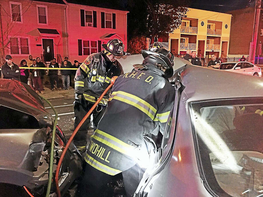 Firefighters use hydraulic rescue tools to free a driver pinned in a car after a crash Tuesday night on Sherman Avenue. Photo: Courtesy Of New Haven Fire Dept.