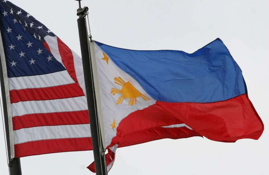 The Filipino flag flies next to the American flag during a flag-raising ceremony at Greenwich Town Hall Friday morning honoring the Philippines declaration of independence from Spain on June 12, 1898. Photo: David Ames, David Ames/For Greenwich Time / Greenwich Time