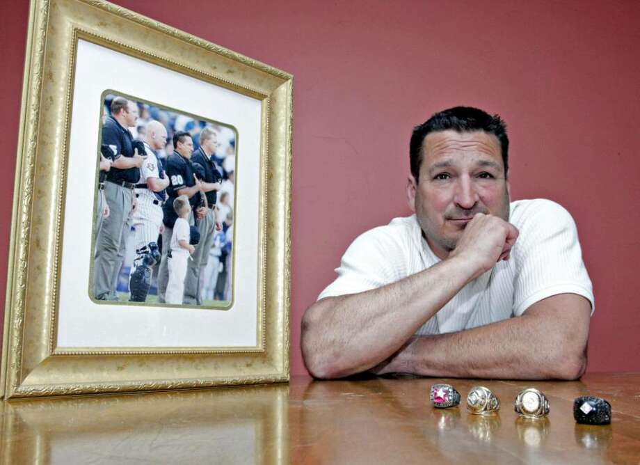 Mark Hirschbeck, a former Major League Baseball umpire, sits for a portrait next to a photograph of him taken before he worked in a  World Series game, at his home in Ansonia, Connecticut, U.S., on Sunday, May 30, 2010. Displayed on the table are two World Series rings and two two All-Star Game rings Hirschbeck received while working for Major League Baseball. A failed hip replacement surgery in 2003 forced Hirschbeck into retirement. The ceramic joint made by Wright Medical Group Inc. shattered, leading to an infection and four more surgeries that left Hirschbeck permanently sidelined. Photographer: Chris Ware/Bloomberg *** Local Caption *** Mark Hirschbeck Photo: Chris Ware, Bloomberg