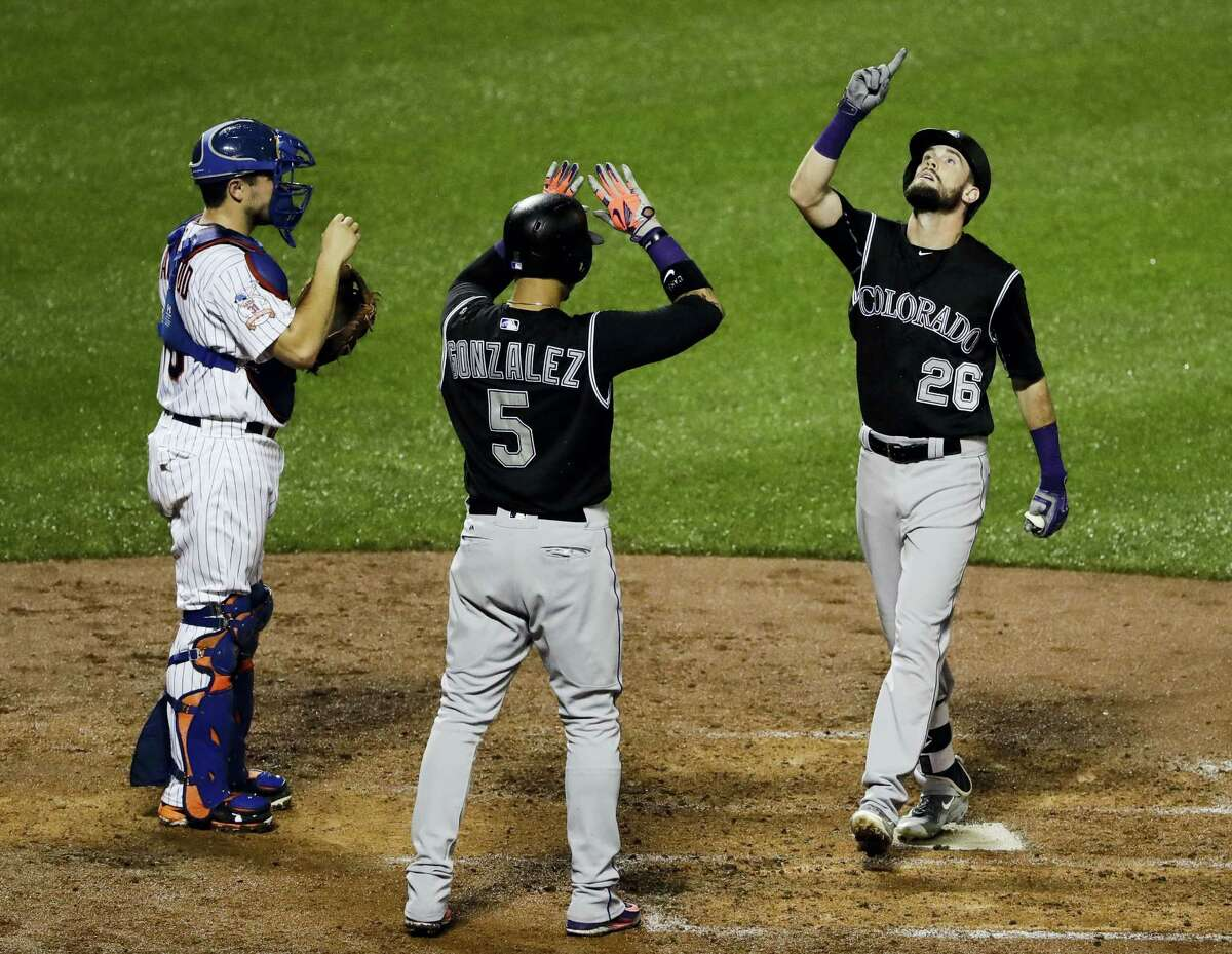 Colorado Rockies' David Dahl (26) and Carlos Gonzalez (5) celebrate after Dahl hit a two-run home run during the fourth inning of a baseball game as New York Mets catcher Travis d'Arnaud, left, watches, Saturday, July 30, 2016, in New York. (AP Photo/Frank Franklin II)