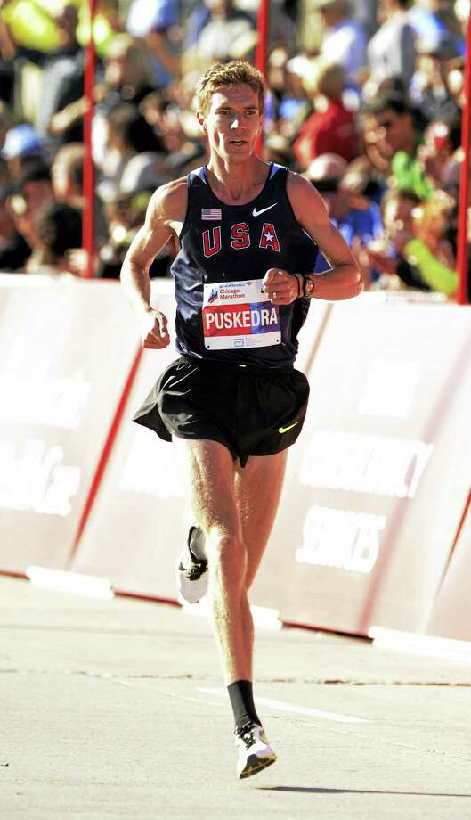 Luke Puskedra, of the United States, finishes fifth during the men's Bank of America Chicago Marathon, Sunday, Oct. 11, 2015, in Chicago. (AP Photo/Paul Beaty) Photo: AP / FR36811
