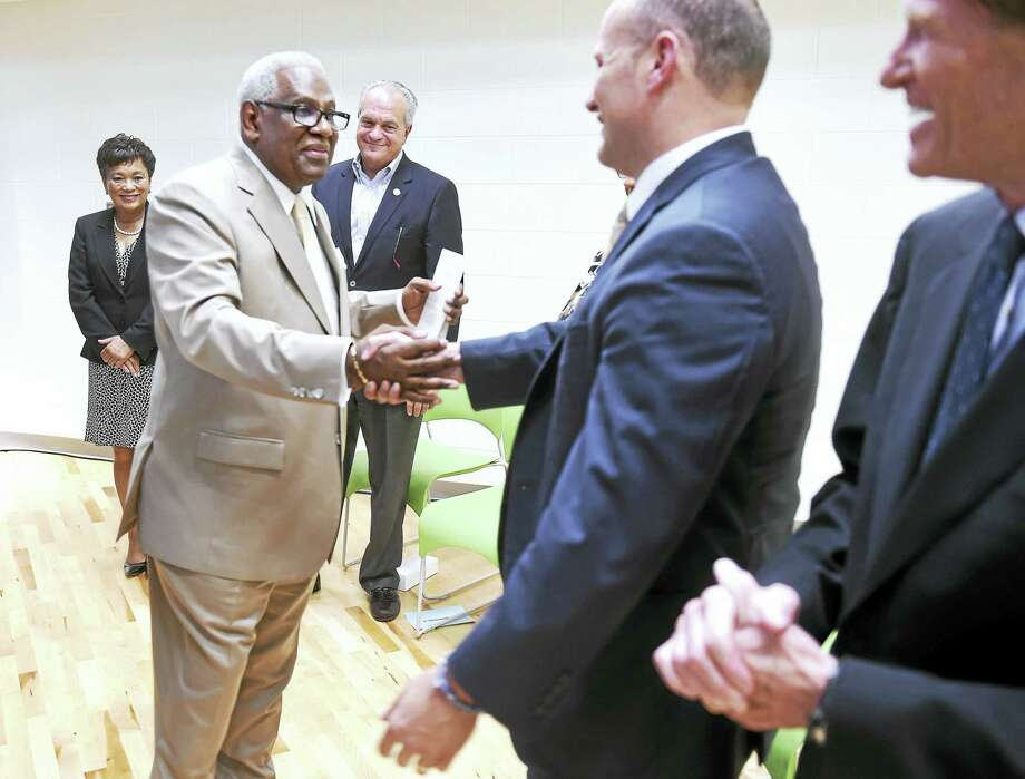 Reginald Mayo, left, shakes hands with outgoing Superintendent of New Haven Public Schools Garth Harries during the dedication ceremony for the Dr. Reginald Mayo Early Learning Center in New Haven on Sunday. Mayo will become the interim superintendent Wednesday. Photo: Arnold Gold -- New Haven Register