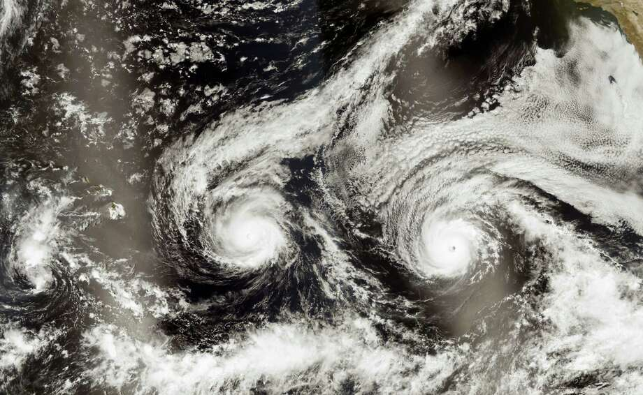 This satellite image taken Monday, Aug. 29, 2016, and released by NASA shows Hurricane Madeline, left, and Hurricane Lester over the Pacific Ocean in a composite built from two overpasses by the Visible Infrared Imaging Radiometer Suite on the Suomi NPP satellite. The National Weather Service issued a hurricane warning as the storm dubbed Madeline churned west Tuesday, Aug. 30, 2016, toward the island, urging residents to rush through preparations to protect themselves and their property and expect hurricane conditions within the next 36 hours. Photo: NASA Via AP    / NASA