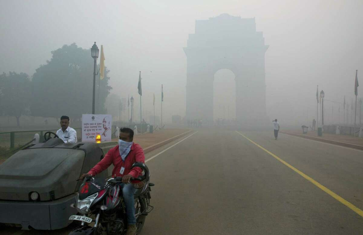 A man covers his face with a scarf as he rides in front of the landmark India Gate, enveloped by smoke and smog, on the morning following Diwali festival in New Delhi, India on Oct. 31, 2016. As Indians wake Monday to smoke-filled skies from a weekend of festival fireworks for the Hindu holiday of Diwali, New Delhi's worst season for air pollution begins, with dire consequences. A new report from UNICEF says about a third of the 2 billion children in the world who are breathing toxic air live in northern India and neighboring countries, risking serious health effects including damage to their lungs, brains and other organs.