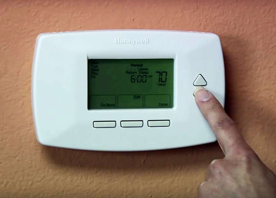"""This image provided by the US Environmental Protection Agency shows a person programming a thermostat for a furnace/HVAX system. Consider investing in a programmable thermostat to maximize energy efficiency. """"We recommend keeping it set to between 68 and 72 degrees when people are home, and then down to between 55 and 65 when no one is home and at night,"""" says Lauren Urbanek, senior energy policy advocate for the Natural Resources Defense Council. Photo: US Environmental Protection Agency Via AP   / US Environmental Protection Agency"""