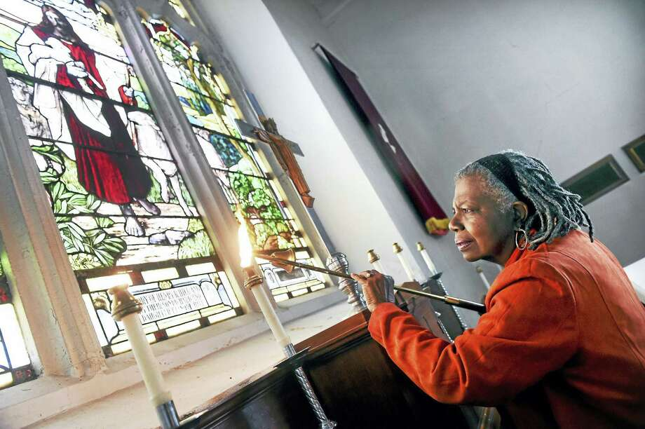 Arnold Gold — New Haven Register  Altar Guild member Carrie Kelly of West Haven lights candles on the altar before services at St. Andrew's Episcopal Church Sunday. Photo: Digital First Media