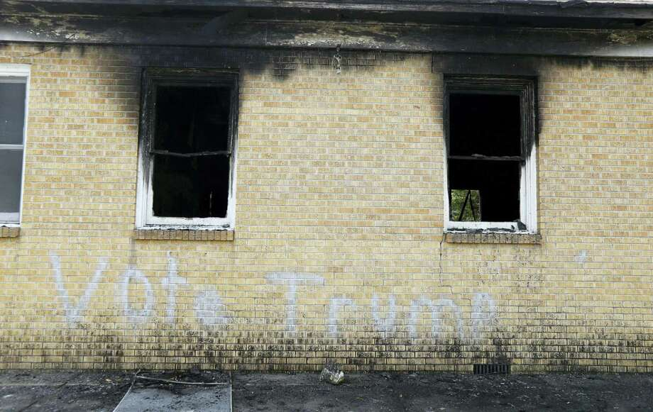 """Vote Trump"" is spray painted on the side of the fire damaged Hopewell M.B. Baptist Church in Greenville, Miss. Mississippi authorities arrested a McClinton Wednesday in the burning of an African-American church that was also spray-painted with the words ""Vote Trump."" Photo: Rogelio V. Solis — AP File Photo   / Copyright 2016 The Associated Press. All rights reserved."