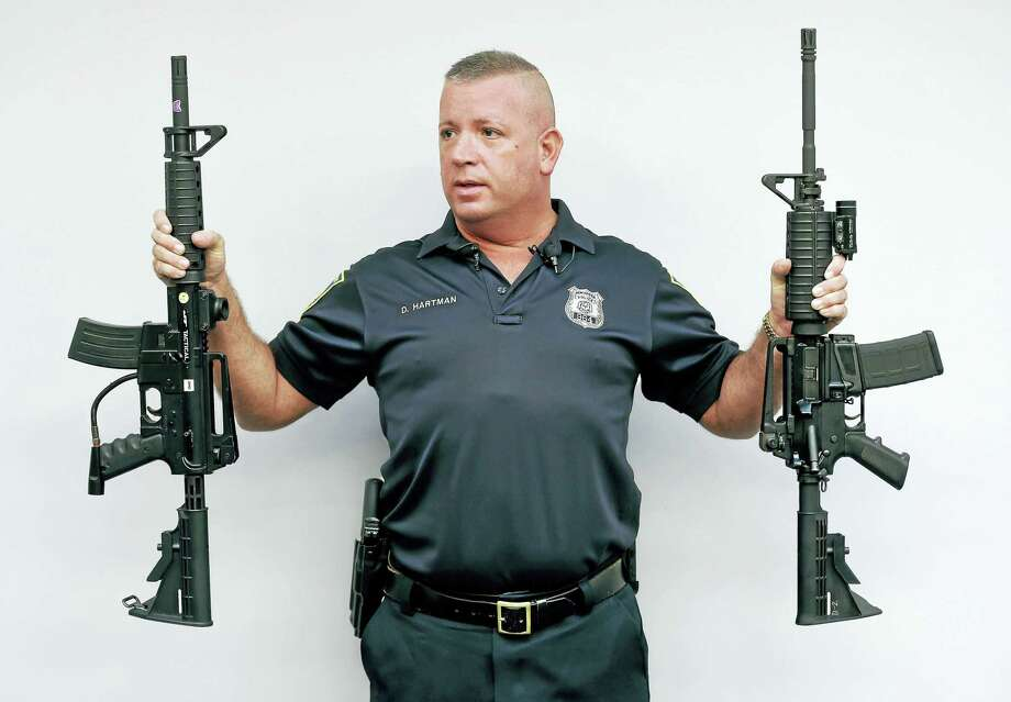 New Haven Police public information Officer David Hartman holds a paintball rife (left) and Colt AR rifle (right) during a press conference at the New Haven Police Department Friday following the department responding to calls of gun battles in New Haven. The guns turned out to be paintball rifles but bear a striking similarity to real rifles. Photo: Arnold Gold-New Haven Register