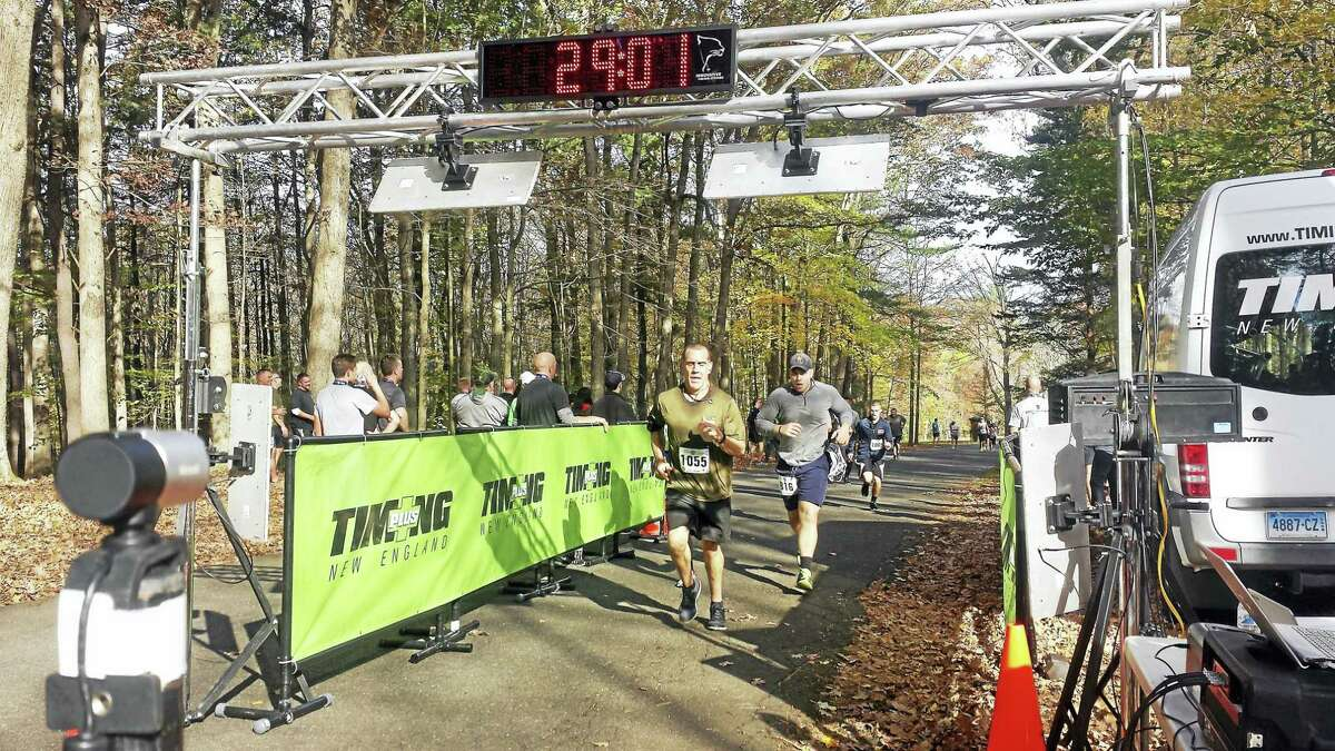 From left, Stephen Faucher (1055), Travis Downing (816) and Michael D'Aresta (1069) race for the finish line at the 29-minute mark.