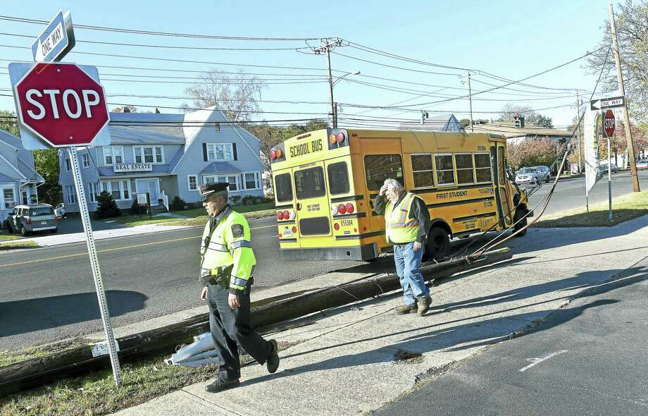 Hamden Police Sgt. Edward Armeno, left, and Hamden Traffic Technician Ted Braza inspect the damage from a bus accident which knocked down a utility pole on Dixwell Ave. in Hamden. No children were on the bus and no one was injured. Photo: Arnold Gold-New Haven Register