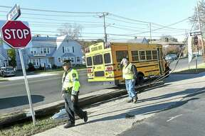 Hamden Police Sgt. Edward Armeno, left, and Hamden Traffic Technician Ted Braza inspect the damage from a bus accident which knocked down a utility pole on Dixwell Ave. in Hamden. No children were on the bus and no one was injured.
