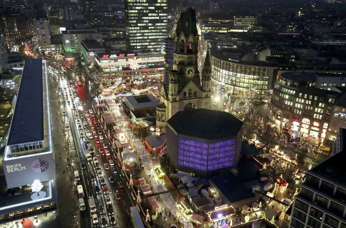 Cars drive past the reopened Christmas market at the Kaiser Wilhelm Memorial Church, center, in Berlin, Germany, Thursday, Dec. 22, 2016, three days after a truck ran into the crowded market and killed several people.