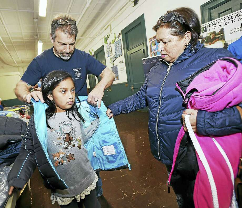 In one of the Knights of Columbus 2016 efforts to help the community, Dan Marfino, a member of K of C Council 3734 at Father James F. Danaher Council 3734 in North Haven, helps Nathalie Rivas, 8, try on a new coat as her grandmother Blanca Calle watches at the K of C Coats for Kids initiative in November at St. Martin de Porres Academy at 208 Columbus Ave., New Haven. Since 2009, more than 370,000 new coats have been distributed from coast to coast. Photo: Catherine Avalone — New Haven Register   / New Haven RegisterThe Middletown Press