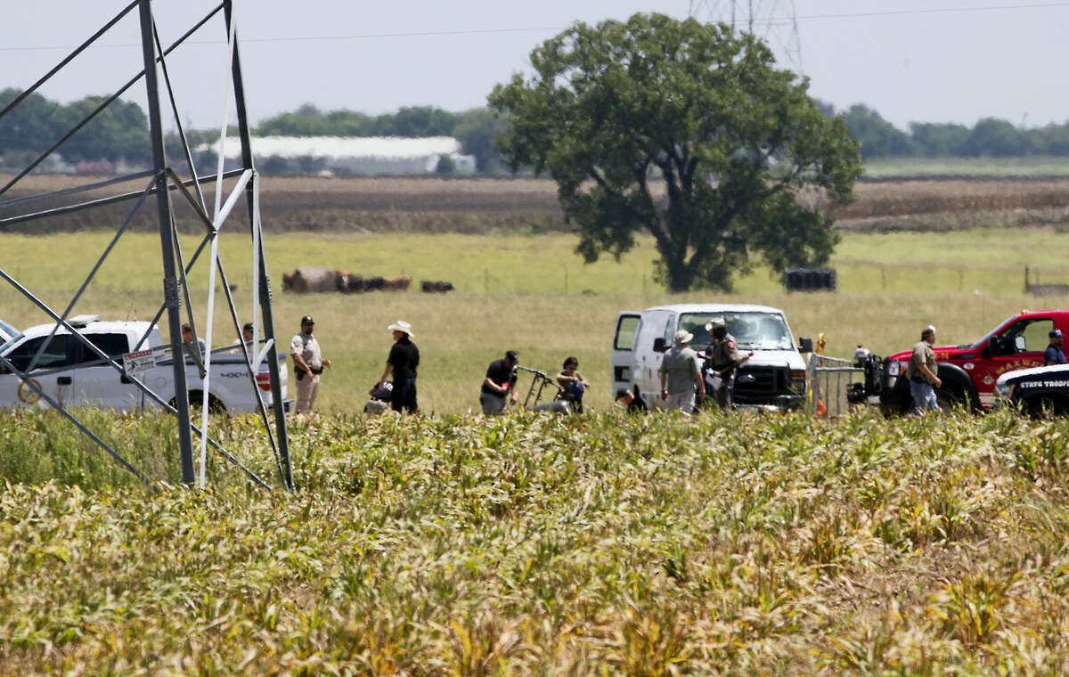 """The partial frame of a hot air balloon is visible above a crop field at the scene in a field near Lockhart, Texas where a hot air balloon carrying at least 16 people collided with power lines Saturday, July 30, 2016, causing what authorities described as a """"significant loss of life."""""""