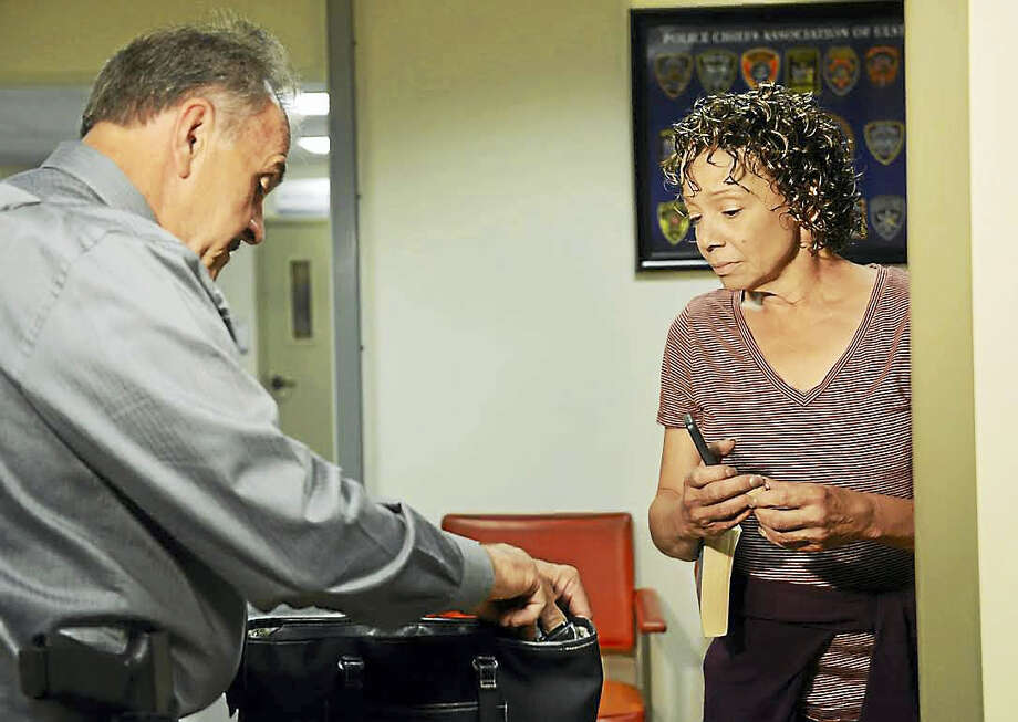 Alison Carey, right, is shown at the Saugerties Town Court security checkpoint on Wednesday. Examining the contents of her bag is Court Officer Thomas Sperl. Photo: Tania Barricklo — Daily Freeman