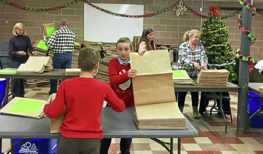 For the past three years, resident Etta Hanlon, in partnership with the town's Solid Waste Department, has created and distributed 4,000 holiday paper bags — similar to a leaf bag — to Branford schools, churches and town departments to educate residents on how to properly recycle paper items during the holiday season. Photo: Contributed Photo