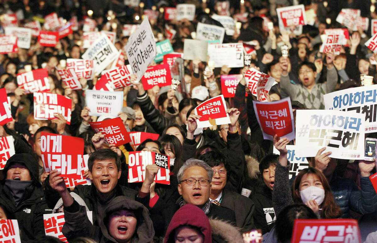 """South Korean protesters shout slogans during a rally calling for South Korean President Park Geun-hye to step down in downtown Seoul, South Korea, Saturday, Nov. 5, 2016. Tens of thousands of South Koreans poured into the streets of downtown Seoul on Saturday, using words including """"treason"""" and """"criminal"""" to demand that Park step down amid an explosive political scandal. The signs read """"Park Geun-hye should step down."""""""