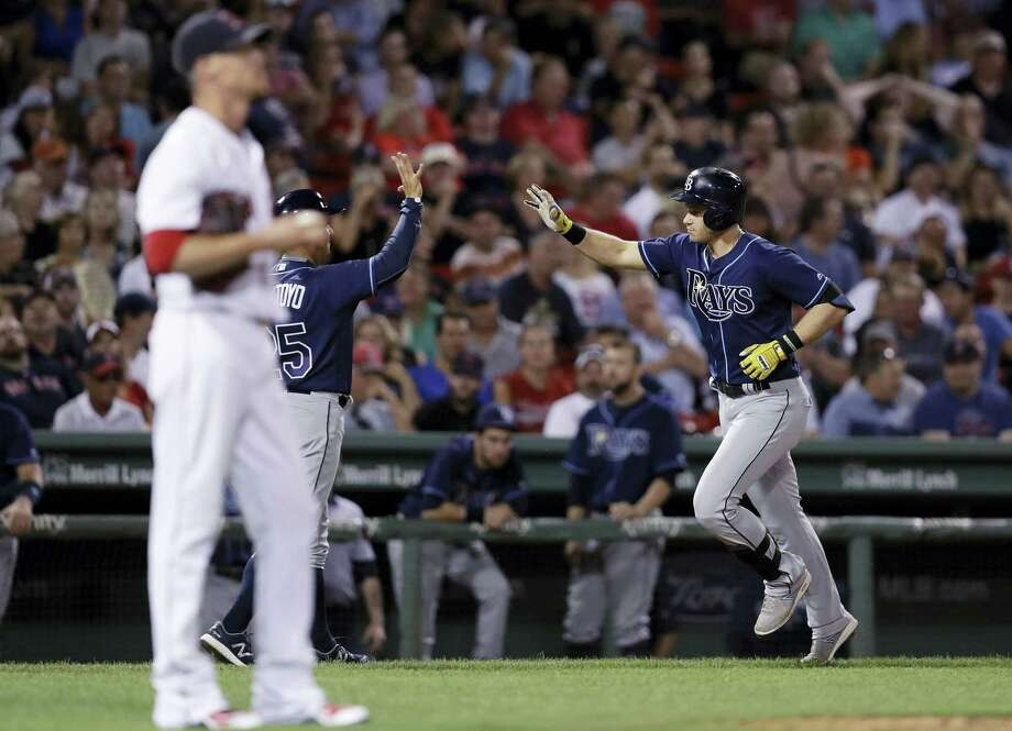 Tampa Bay's Evan Longoria, right, is congratulated by third base coach Charlie Montoyo after his solo home run off Boston Red Sox pitcher Clay Buchholz during the eighth inning at Fenway Park Tuesday. The Rays won 4-3. Photo: CHARLES KRUPA — The Associated Press   / AP