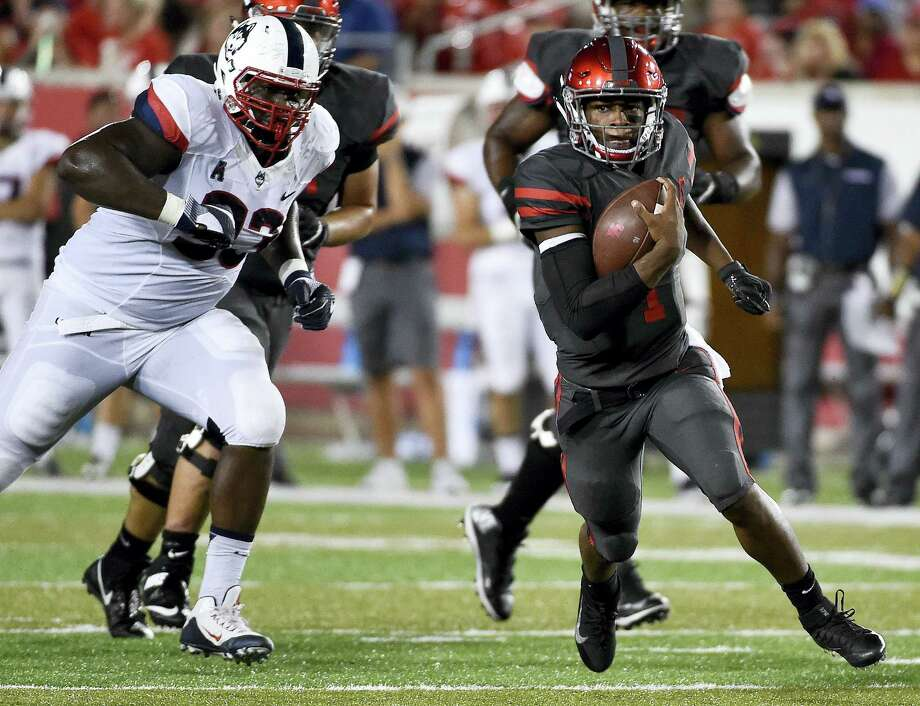 Houston quarterback Greg Ward Jr. (1) runs past UConn defensive lineman Folorunso Fatukasi, left, en route to a 30-yard touchdown in the first half on Thursday. Photo: Eric Christian Smith — The Associated Press   / FR171023 AP
