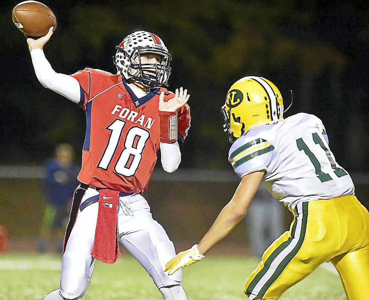 Foran QB Lance DiNatale looks to make a pass during a win over New London last season at Vino DeVito Sports Complex at Foran High School in Milford.