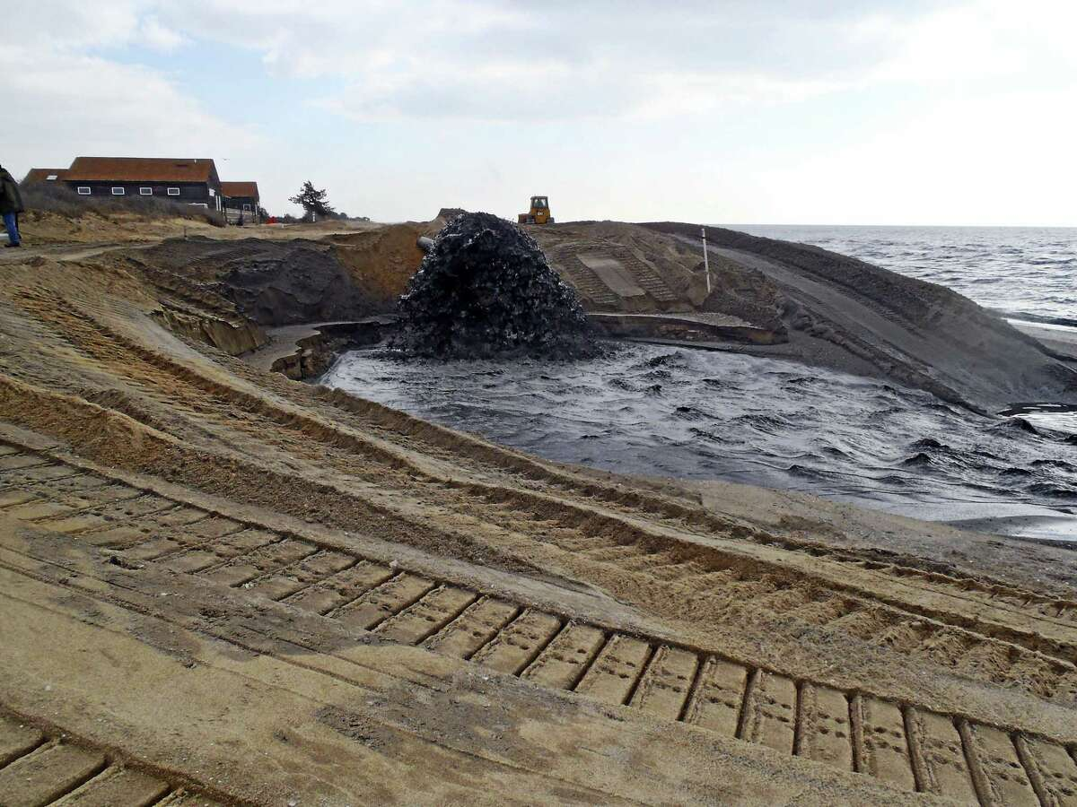 Sand was pumped one mile from Clinton Harbor Channel to the western end of Hammonasset Beach State Park in 2013. The sand pictured here comes out in a slurry, according to the Connecticut Port Authority, and the water drains out leaving sand behind. (Submitted Photo/CT Port Authority)