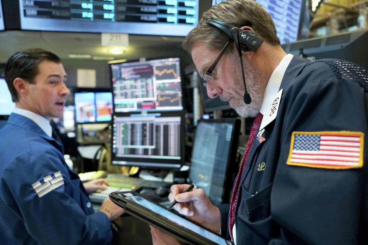 Stock trader Luke Scanlon, right, works at the New York Stock Exchange Thursday in New York.
