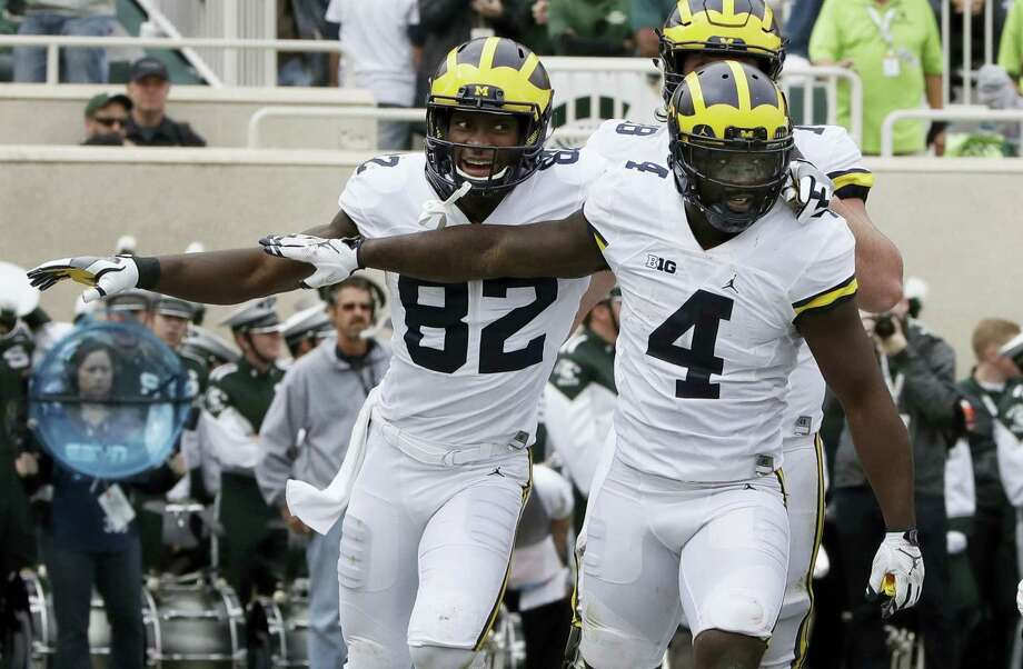 Michigan running back De'Veon Smith (4) is congratulated by wide receiver Amara Darboh (82) after his 5-yard run for a touchdown during the first half on Saturday. Photo: Carlos Osorio — The Associated Press   / Copyright 2016 The Associated Press. All rights reserved.