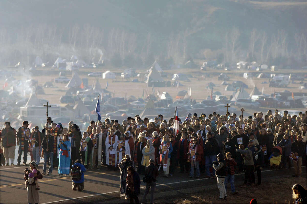 A long procession of hundreds clergy of numerous denominations and faiths walk on Highway 1806 from the Oceti Sakowin encampment to the site of the violent clash with law enforcement with Dakota Access Pipeline protesters, Thursday, Nov. 3, 2016 in Morton County, N.D. (Mike McCleary/The Bismarck Tribune via AP)