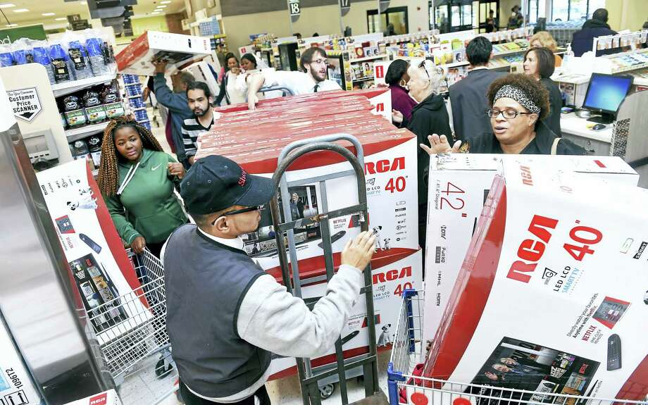 Yesmail Perez (center) helps customers with televisions on sale for the grand opening of ShopRite on Bull Hill Lane in Orange Sunday. Photo: Arnold Gold — New Haven Register