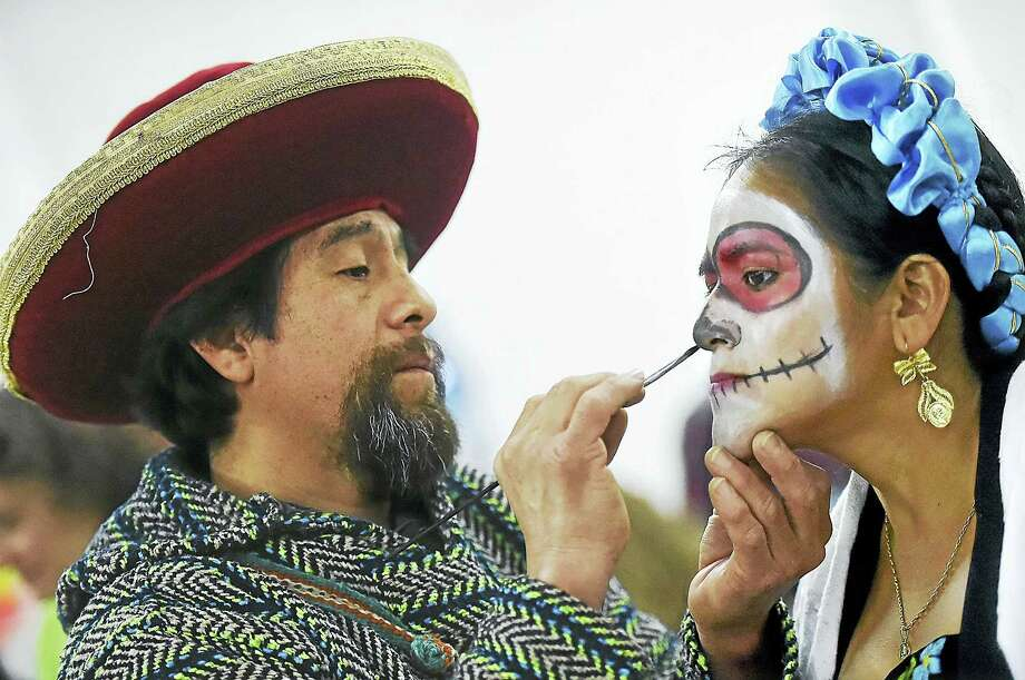 Bridgeport artist Miguel Angel Mendoza paints the face of Maria Antonio, of Bridgeport in preparation of the Carnaval del Dia de los Muertos — Day of the Dead parade, Saturday, November 5, 2016, at 26 Mill St. in New Haven. Both Mendoza and Antonia emigrated from Mexico. Photo: Catherine Avalone — New Haven Register / New Haven RegisterThe Middletown Press