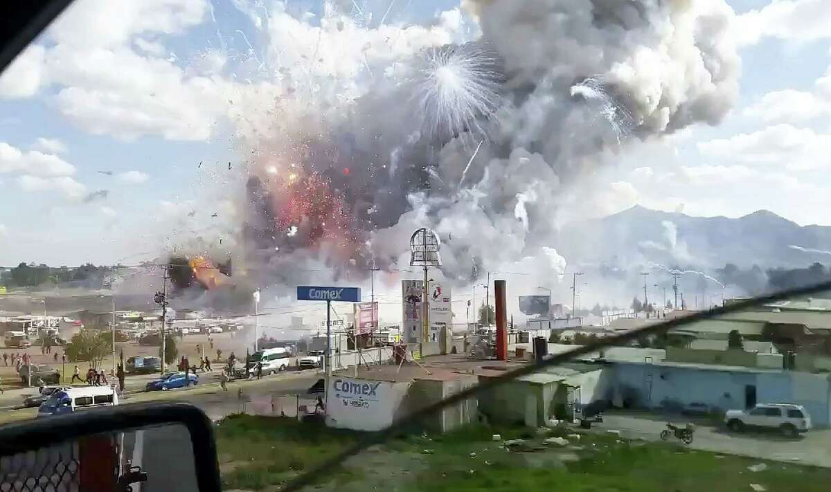 This image made from video recorded from a passing car shows an explosion ripping through the San Pablito fireworks' market in Tultepec, Mexico, Tuesday, Dec. 20, 2016. Sirens wailed and a heavy scent of gunpowder lingered in the air after the afternoon blast at the market, where most of the fireworks stalls were completely leveled. According to the Mexico state prosecutor there are at least 29 dead.
