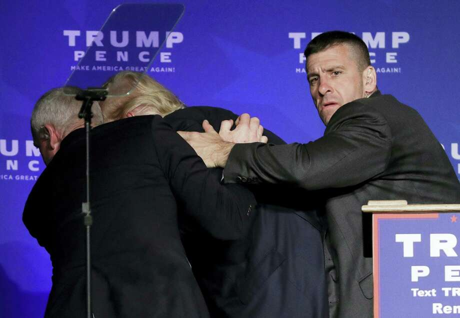 Secret Service agents rush Republican presidential candidate Donald Trump off the stage during a campaign rally in Reno, Nev., on Saturday, Nov. 5, 2016. He returned to the podium afterwards. Photo: John Locher — AP Photo / Copyright 2016 The Associated Press. All rights reserved.