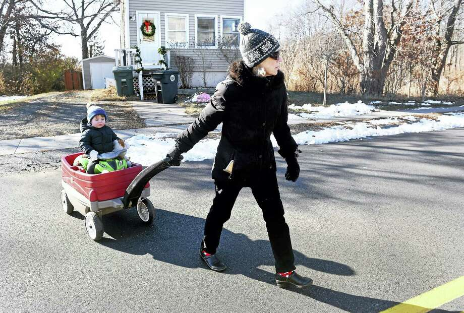 Anne Swartout of Ridgefield crosses the street with her grandson, Calvin, 1, of Milford on their way to Eric Zimmerman Playground in Milford on Tuesday. Photo: Arnold Gold — New Haven Register
