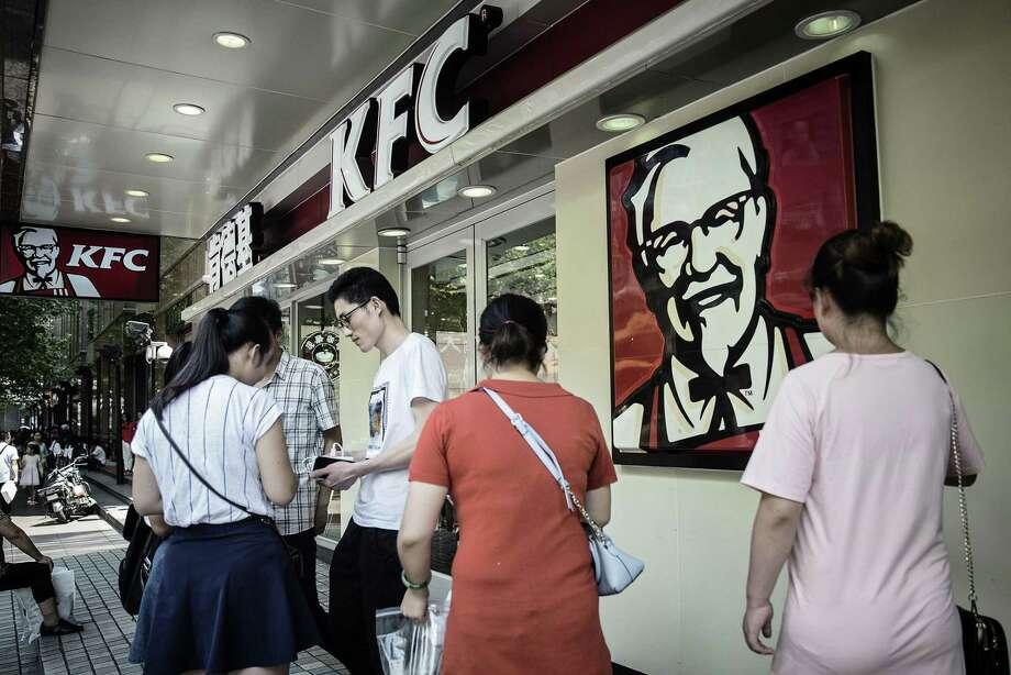 Pedestrians walk past a Yum Brands KFC restaurant in Shanghai, China. Photo: Qilai Shen — Bloomberg   / © 2016 Bloomberg Finance LP